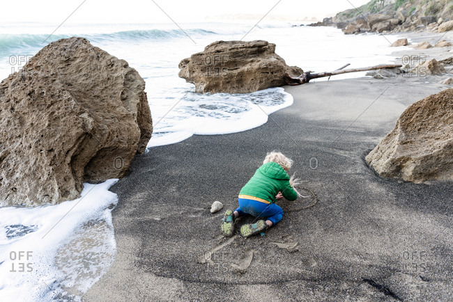 Small child writing in sand on beach in New Zealand