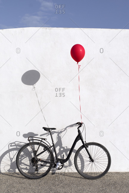 Lonely bike with a balloon attached, leaning against a white