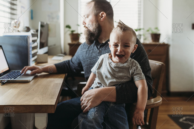 Father trying to work from home with toddler screaming in his lap