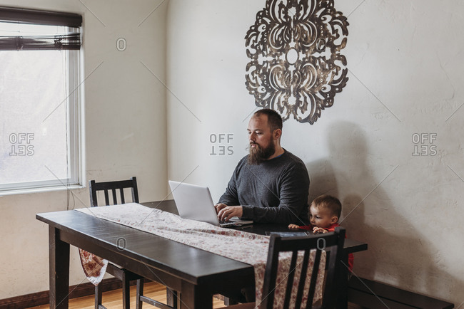 Wide view of father trying to work from home with toddler standing