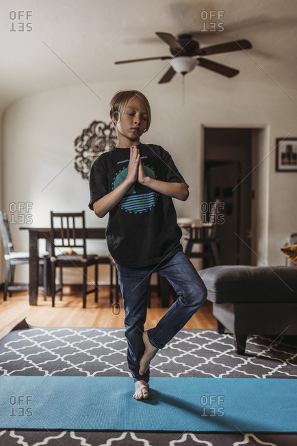 School-age boy doing yoga in living room during isolation