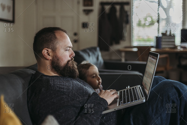Close up of Dad working from home with young daughter