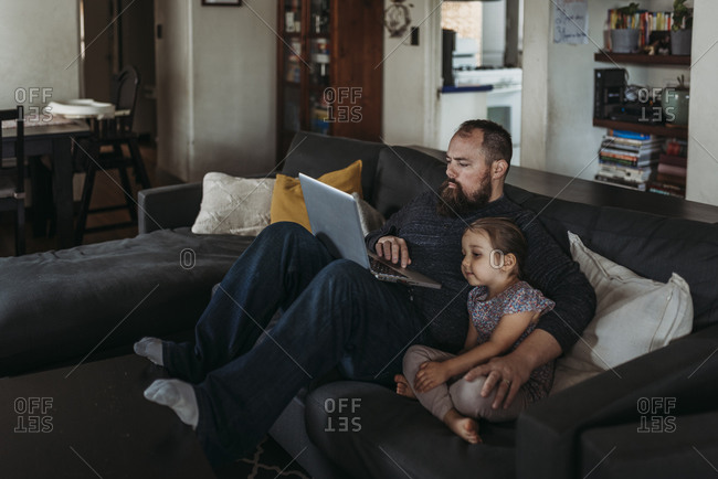 Father working from home with young daughter during isolation