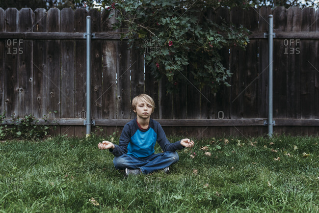 Young boy doing yoga in yard during isolation