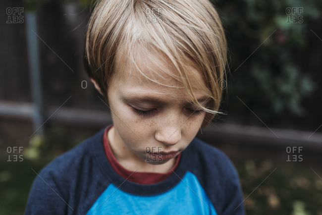 Close up of young boy with eyes closed and freckles