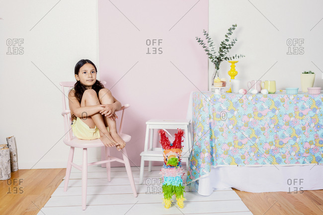 Girl sitting in pink chair at Eastern home party table decor