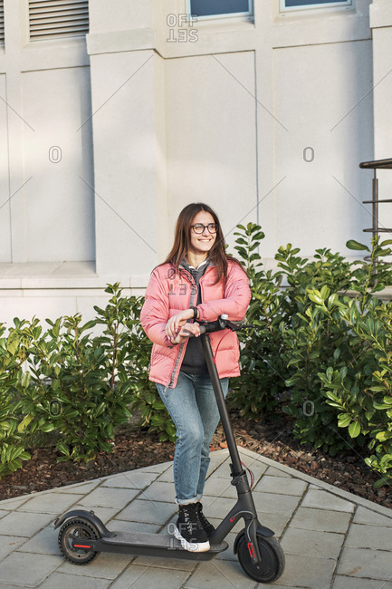 Millennial young girl in a pink jacket on an electric scooter