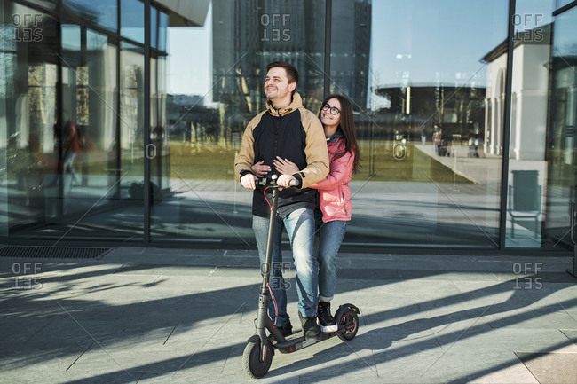 Loving young millennials having fun walking on an electric scooter