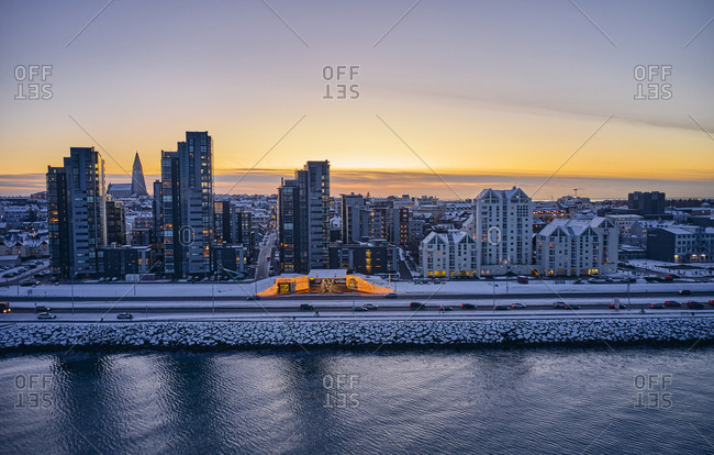 Snowy road and high rise buildings near water in evening