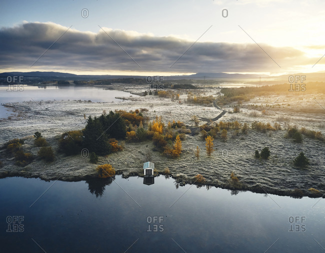 Snowy terrain and lake in autumn day
