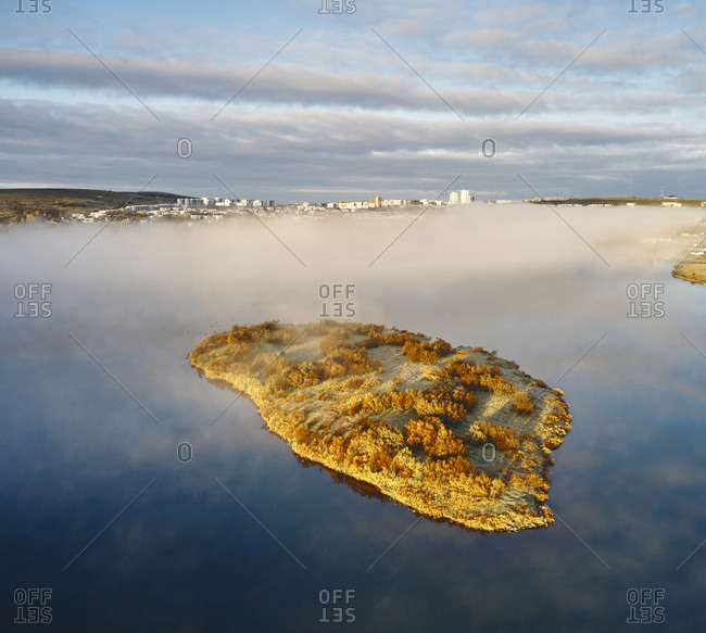 Island and lake in foggy evening time