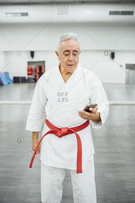 Senior Karate master using mobile cell phone