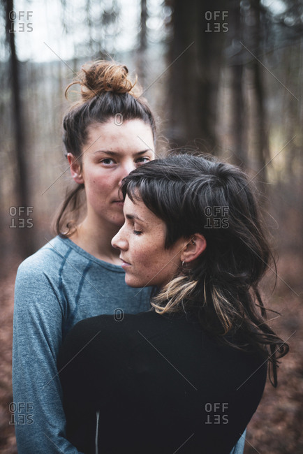 Queer female couple embrace in peaceful moment in winter forest