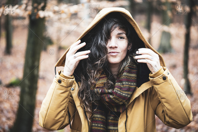 Natural girl in winter jacket smiles in golden bronze autumn forest