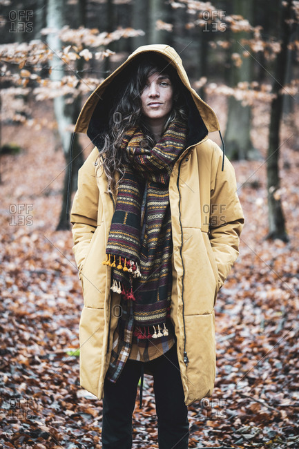 Strong natural woman with curly hair stands empowered in autumn woods
