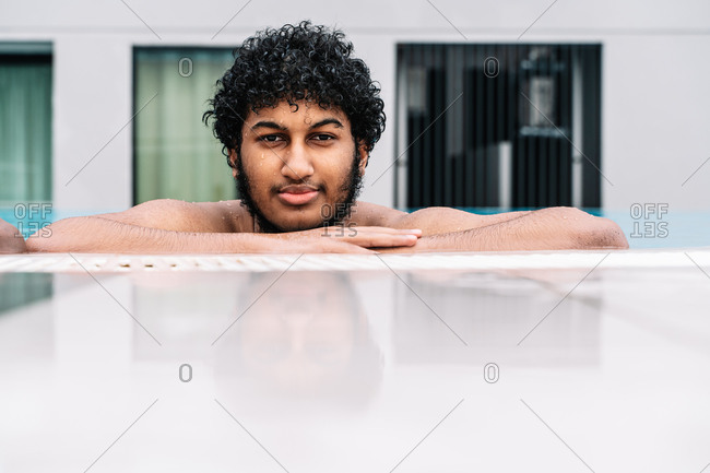 Young Arabian man with curly hair leaning on the edge of a pool