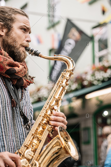 Vertical photo of a saxophonist bearded and with blonde hair playing in the street