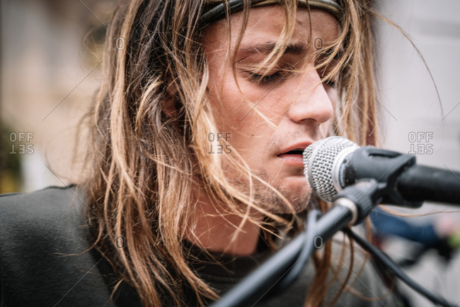 Detail of the face of a young rocker singing with emotion in the street