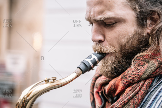 Face of saxophonist with long hair and beard playing in the street