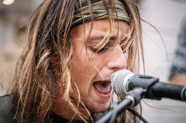 Face of a young rocker singing in the street