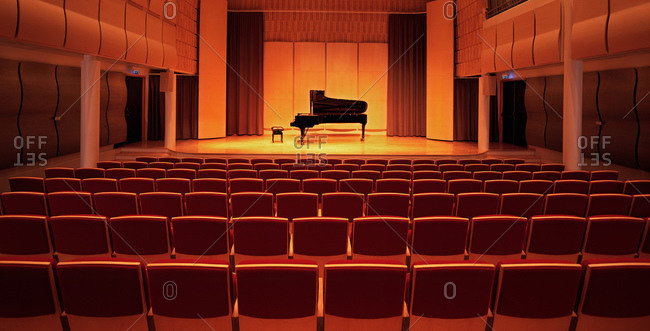 Piano on stage inside an empty concert hall