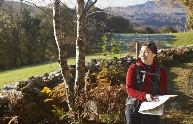 Mature female hiker reading map