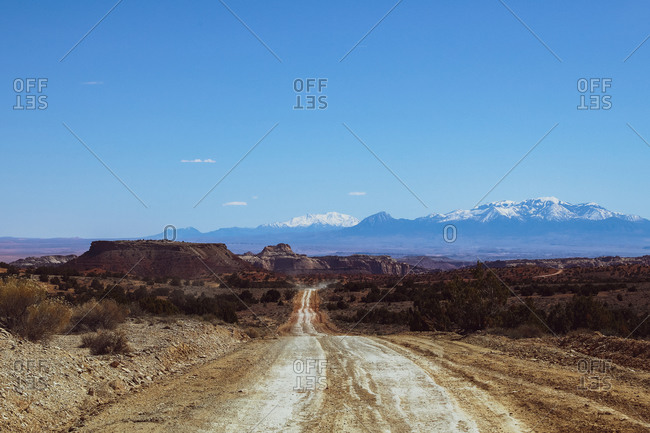 Empty back dirt roads in Utah with mountains in distance