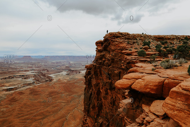 Man alone in far distance standing on large rock ledge over canyonland