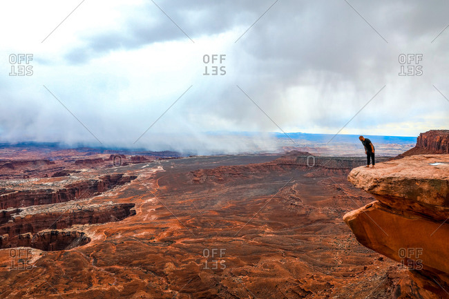 Man looking over canyonlands at the edge of a large rock