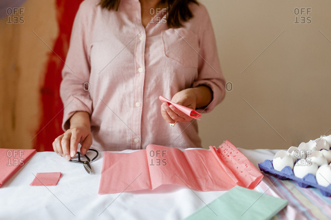 Woman cutting craft pink paper by eggshells at home