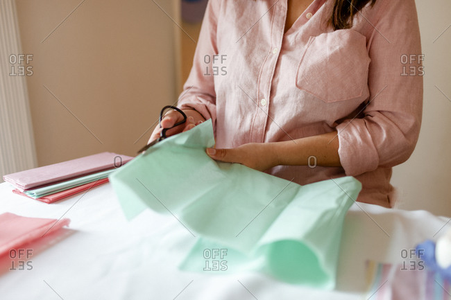Cropped woman cutting green tissue paper during tutorial