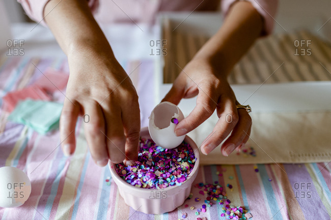 Cropped view lady filling eggs with colorful confetti