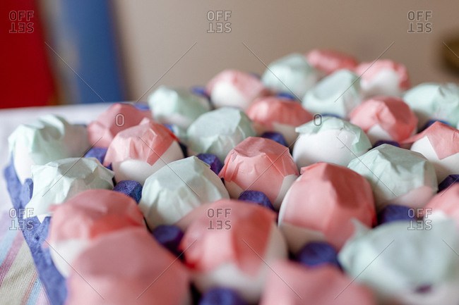Closeup of carton eggs covered by colorful paper