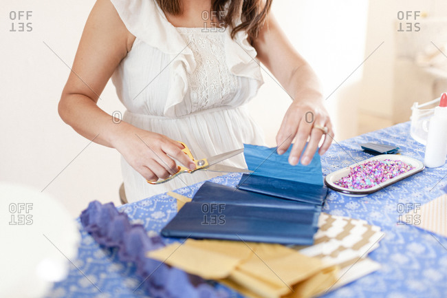 Closeup woman by art table cutting gold tissue paper with scissors