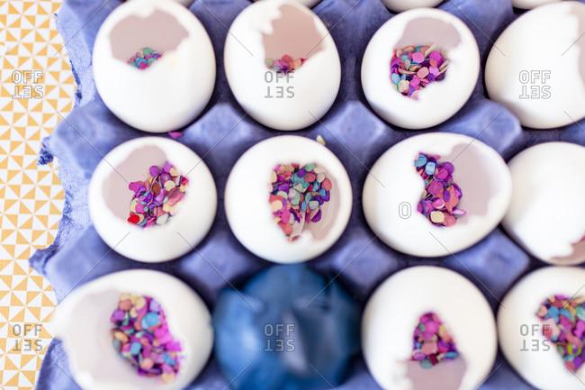 Close-up multi color confetti and eggshells over cloth table