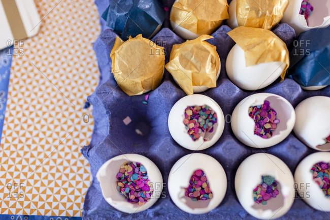 Closeup inside eggshells multicolor confetti and gold and white paper