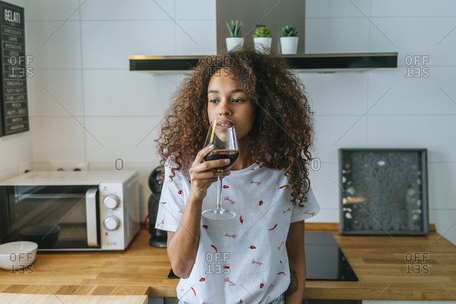 Young woman in the kitchen drinking wine