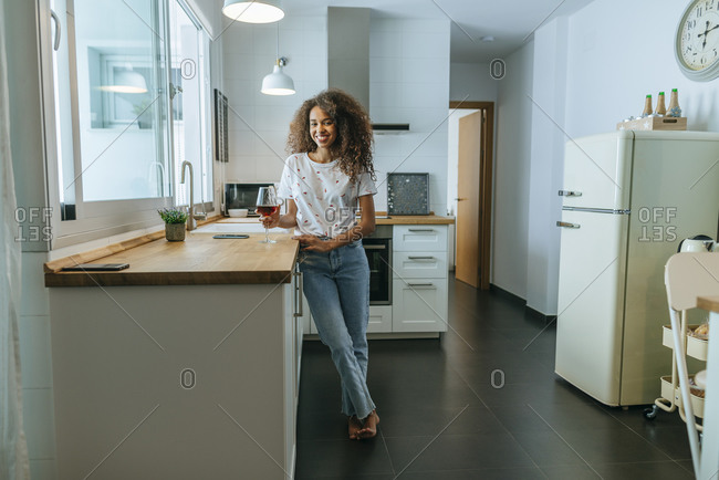 Happy young woman in kitchen with glass of wine looking at camera
