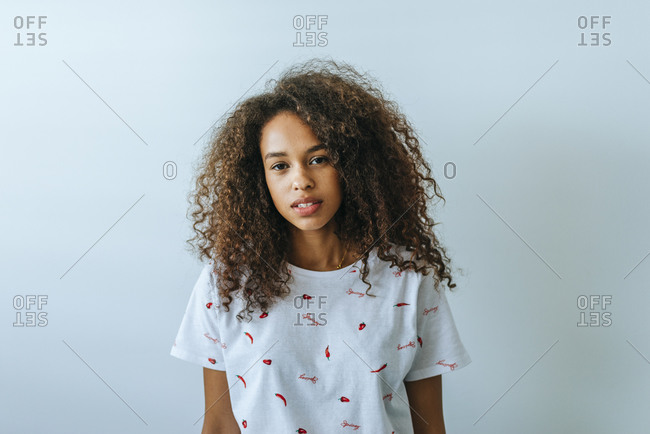 Portrait of woman with afro hair looking at camera, in front of white wall.