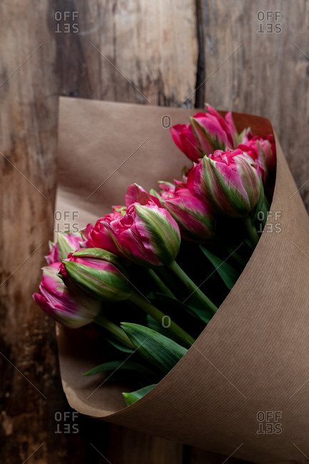 Bouquet of pink tulips wrapped in brown paper