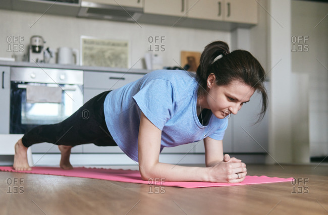 Woman planking on a mat in her kitchen
