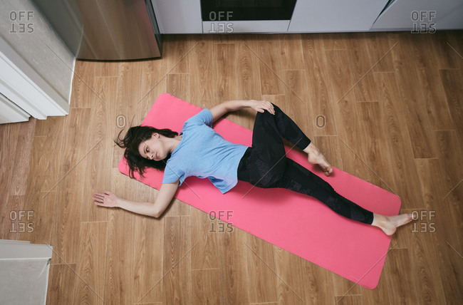 Overhead view of woman stretching on a yoga met in a small apartment