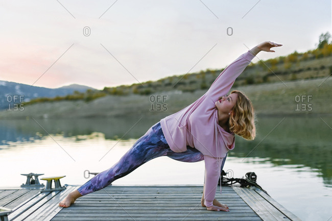 Young woman doing yoga on a jetty- triangle pose