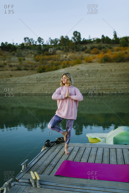 Young woman doing yoga on a jetty- tree pose