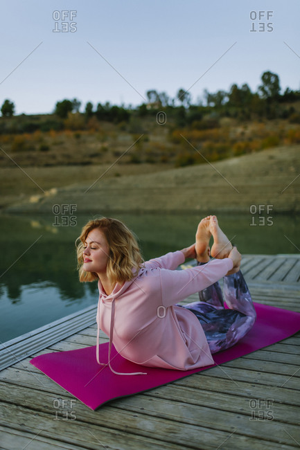 Young woman doing yoga on a jetty- bow pose