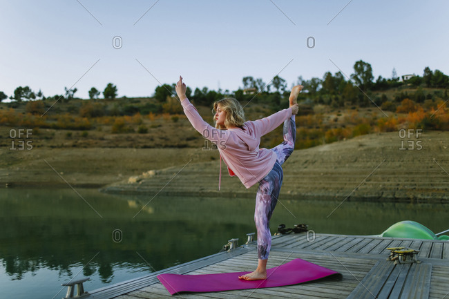 Young woman doing yoga on a jetty- dancer position