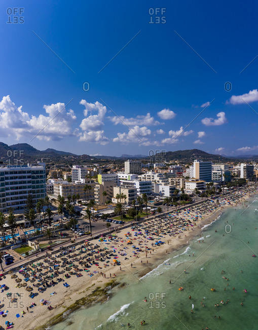 August 23, 2019: Spain- Balearic Islands-CalaBona- Aerial view of sky over resort town and crowded beach in summer
