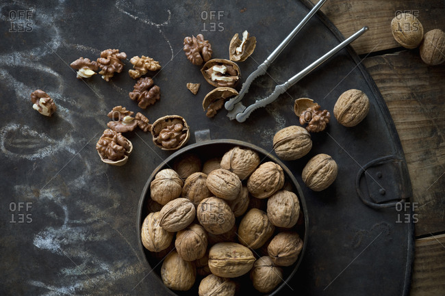 Walnuts and old-fashioned nutcracker lying on rustic baking sheet