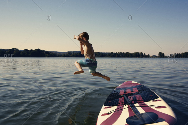 Boy jumping from SUP board into lake at evening twilight