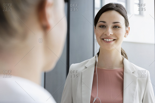 Portrait of smiling young businesswoman with earphones and colleague in office